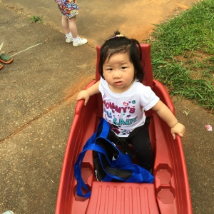 She enjoys riding in her wagon.